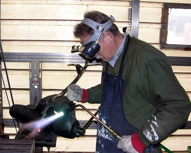 Сварщик использует газовую сварку в работе